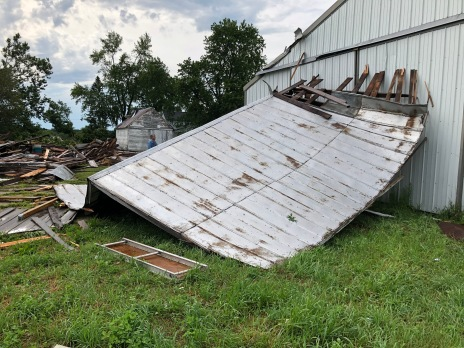Part of the old barn's roof flew off and impaled in the machine shed. The hay trolley track went through the door of the shed.